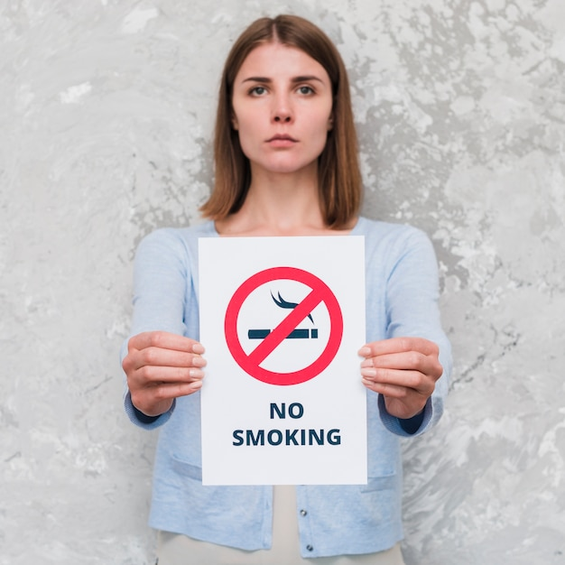 Serious young woman holding social message paper of no smoking Free Photo
