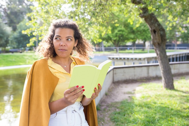 Serious young woman reading book in city park Free Photo