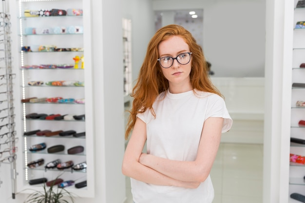 Serious young woman standing in optics shop with arm crossed Free Photo