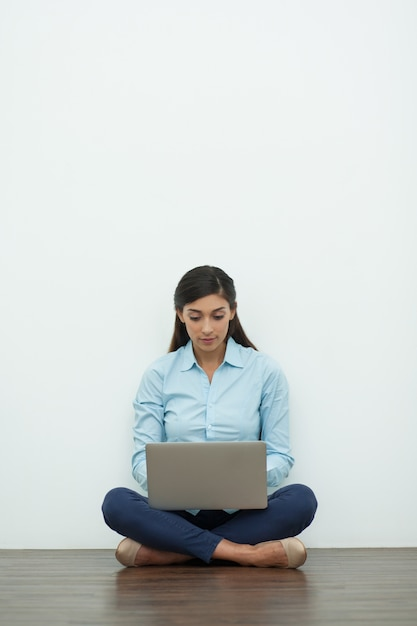 Serious Young Woman Working On Laptop On Floor Photo