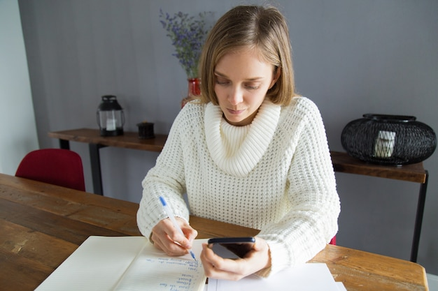 Serious young woman writing down task in notepad Free Photo