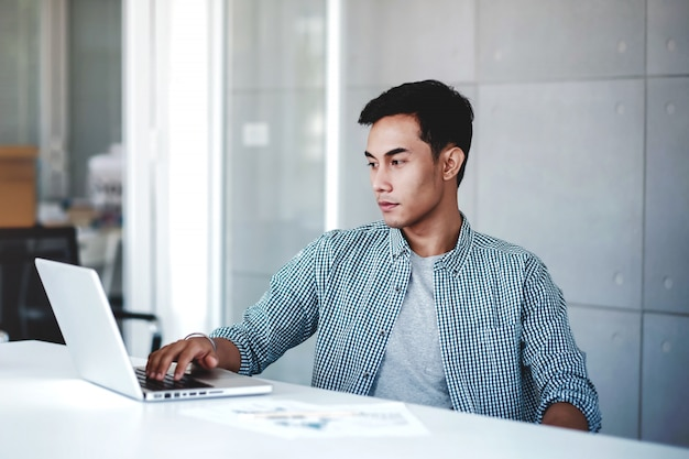 Seriously young businessman working on computer laptop in office. Premium Photo
