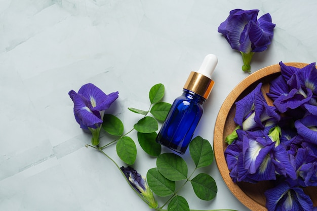 Serum bottle of butterfly pea flower oil put on white marble background Free Photo
