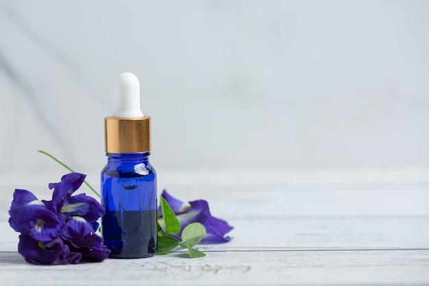 Serum bottle of butterfly pea flower oil put on white wooden floor Free Photo
