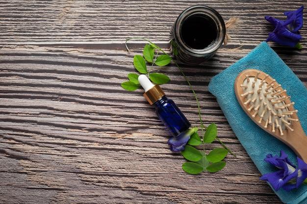 Bottiglia di siero di olio di fiori di pisello farfalla messo su sfondo di legno Foto Gratuite