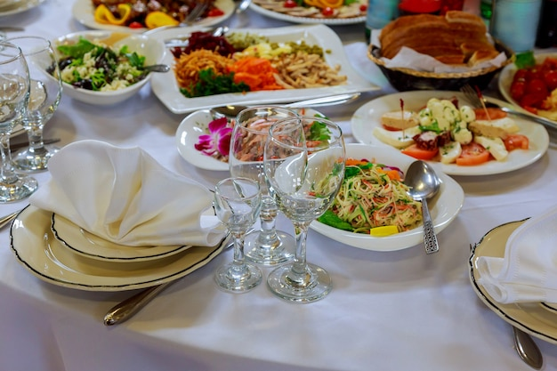 Served for banquet table. wine glasses with napkins, glasses and salads. Premium Photo