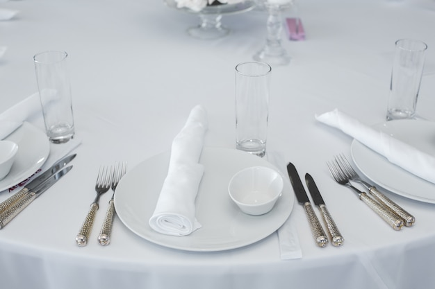 Served table in the restaurant. clean white dishes layout on a white tablecloth. Premium Photo