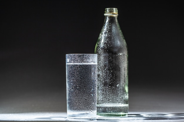 Served table set of mineral water bottle and glass Premium Photo