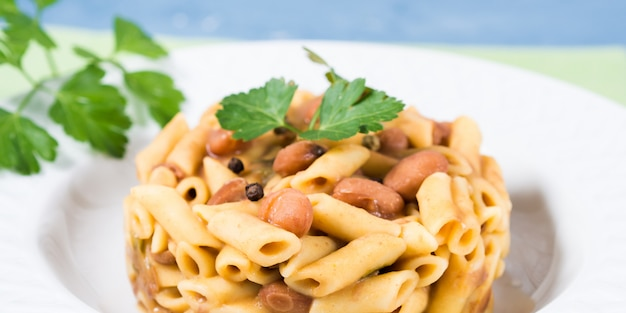 Served traditional italian penne pasta with kidney beans on white plate and blue Premium Photo