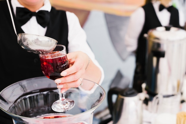 Server pouring sangria with ladle Free Photo