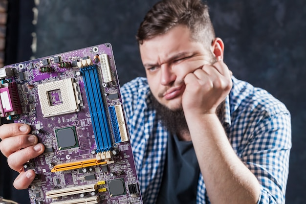 Service engineer fixing problem with computer motherboard. repairman makes electronic components diagnostic Premium Photo