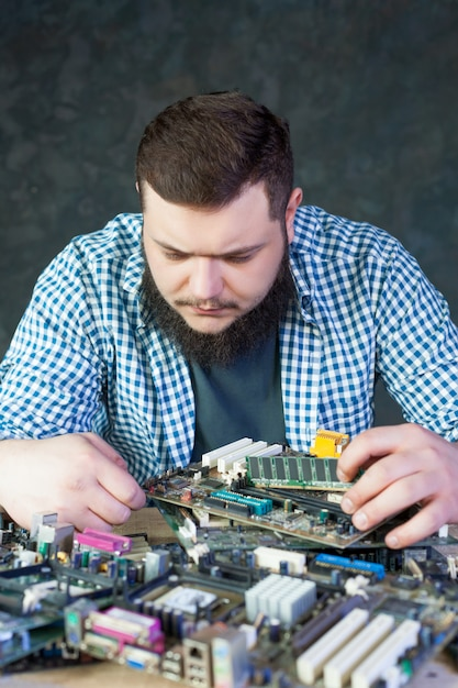 Service engineer work with broken computer motherboard. electronic components repairing technology Premium Photo