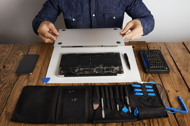 Service man opens backside topcase cover of computer laptop before repairing, cleaning and fixing it with his professional tools from toolkit box near on wooden table front view Free Photo