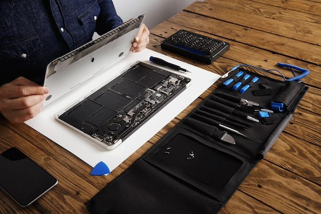 Service man opens backside topcase cover of computer laptop before repairing, cleaning and fixing it with his professional tools from toolkit box near on wooden table Free Photo