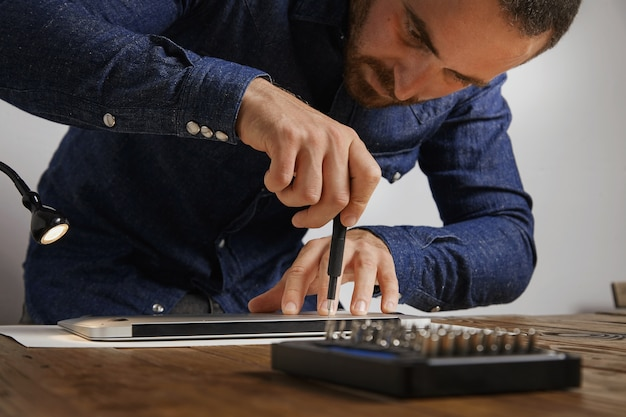 Serviceman uses screwdriver to close backside topcase of personal computer laptop after repairing and cleaning service in his lab Free Photo