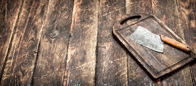 배경 봉사. 도 마 보드에 오래 된 도끼입니다. 나무 테이블에. 프리미엄 사진