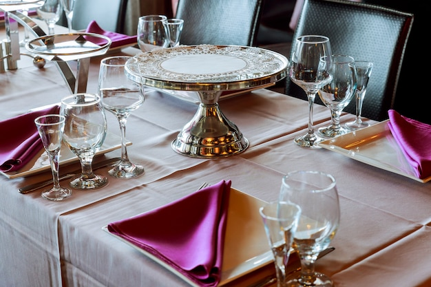 Serving table in restaurant with wine glasses and cutlery. Premium Photo