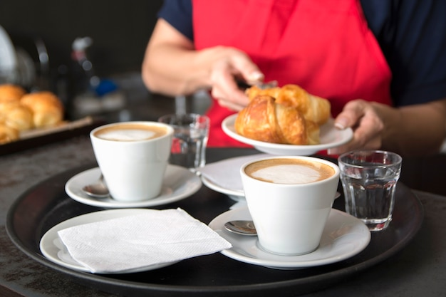 Serving two coffee cups in front of the waitress placing croissant in the plate Free Photo