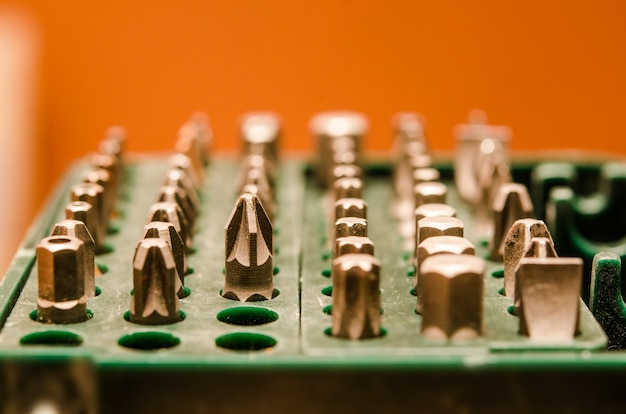 Set of bits for screwdriver in a green case on a orange background. Premium Photo