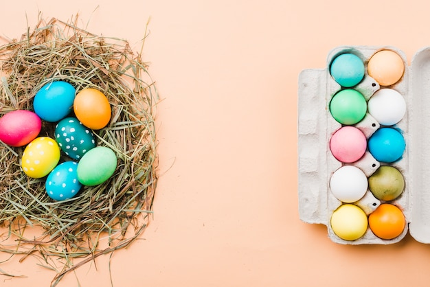 Set of bright easter eggs in nest and container Free Photo