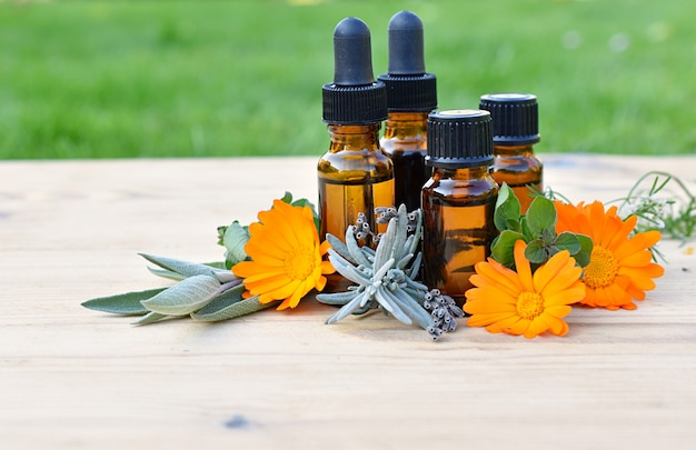 Set of brown bottles with essential and cosmetic oils, fresh herbs and flowers, aromatherapy, phytotherapy. Premium Photo