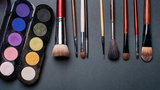 Set of brushes and pallets with colored eye shadows Premium Photo