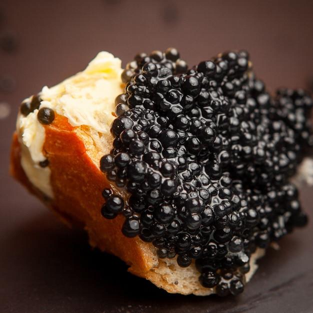 Set di burro e caviale nero su un pane su sfondo scuro. veduta dall'alto. Foto Gratuite