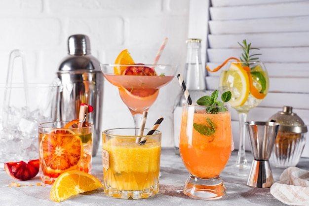 Set of classic cocktails of gin tonic with orange, with lime and mint leaves in glasses Premium Photo