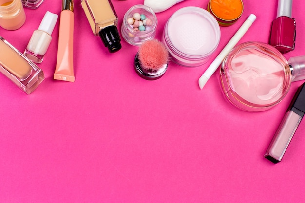 Set of colorful cosmetics on pink table background Premium Photo