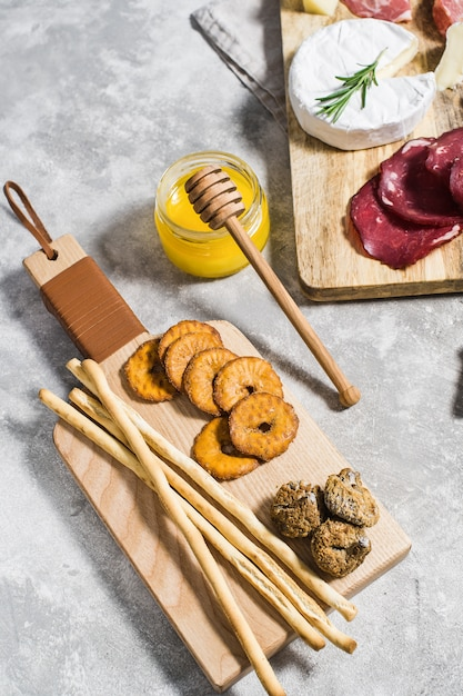 Set of crackers on wooden chopping board, honey. Premium Photo
