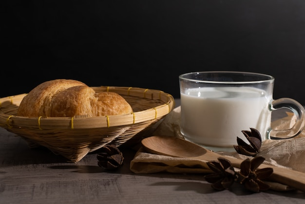 A set of croissant and cup of milk on the wooden table Premium Photo