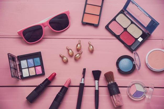 Set of decorative cosmetics for women on pink wood background Premium Photo