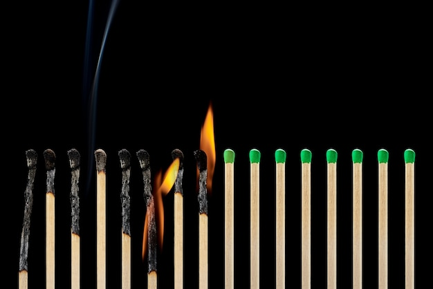 Set of different burnt matches with smoke on a black background. concept of compliance with social distancing Premium Photo