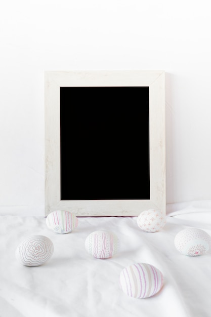 Set of easter eggs near photo frame on textile Free Photo