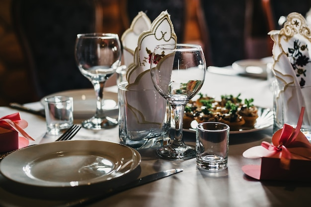 Set of empty glasses and plates with cutlery on a white tablecloth on the table in the restaurant Premium Photo