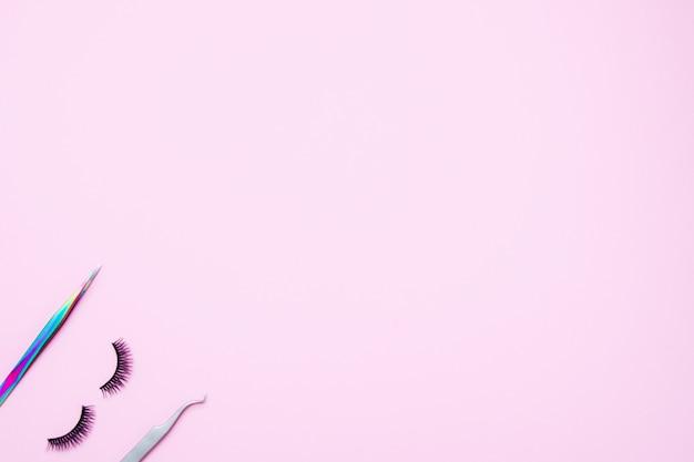 Set for eyelash extension on a pink background. concept beauty beauty. false eyelashes and tweezers Premium Photo