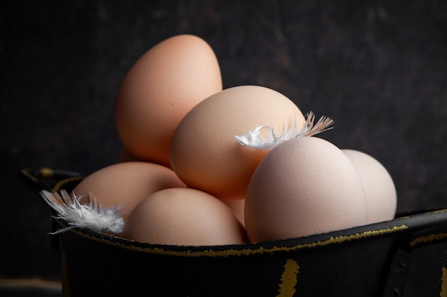 Set of feathers and eggs in a pot on a dark wooden background. close-up. Free Photo
