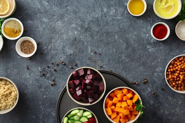 健康的な菜食主義の食糧を調理するための食糧を置きなさい。香辛料入りのヒヨコ豆、焼きカボチャとビート、キノアと野菜。 Premium写真