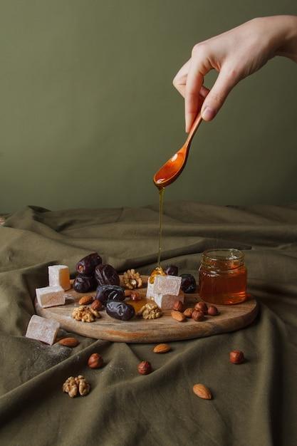 お茶を飲むためのセット。はちみつが滴るスプーンを持っている手。木製のまな板にお茶用のさまざまなお菓子、ナッツ、蜂蜜。ヘルシースイーツ、美味しいデザート、ナチュラルスイーツ。 Premium写真