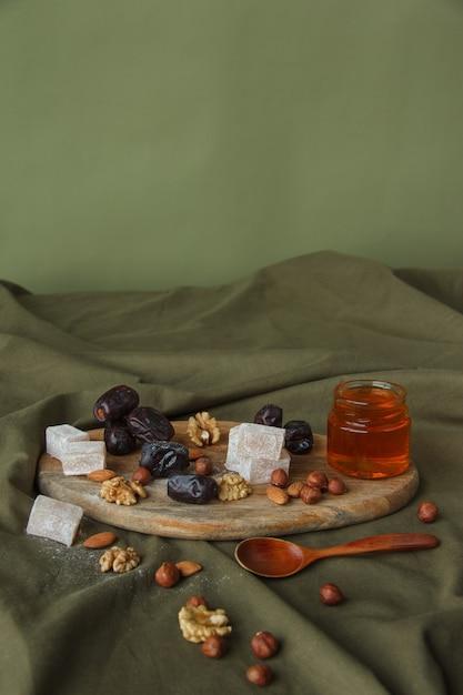 お茶を飲むためのセット。木製のまな板にお茶用のさまざまなお菓子、ナッツ、蜂蜜。クルミ、アーモンド、ヘーゼルナッツ、デート、ラハトルクム、蜂蜜、ドライフルーツ。ヘルシースイーツ、ナチュラルスイーツ。 Premium写真