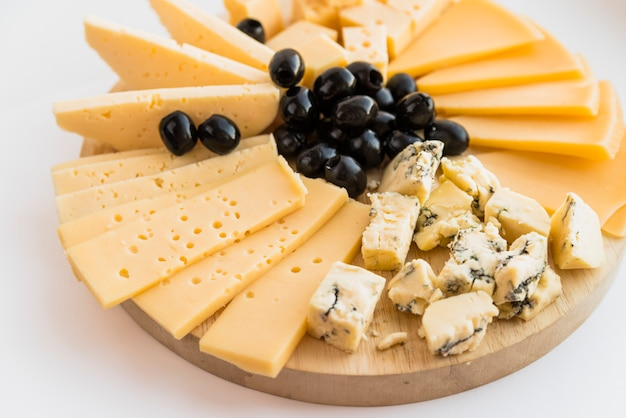 Set of fresh cheese and olives on wood chopping board Free Photo