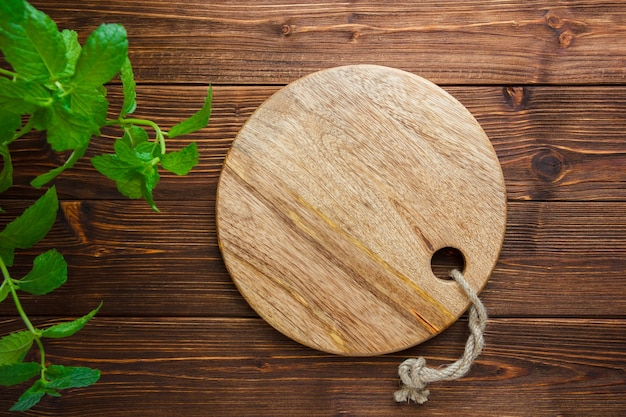 Set of leaves and cutting board on a wooden background. top view. copy space for text Free Photo