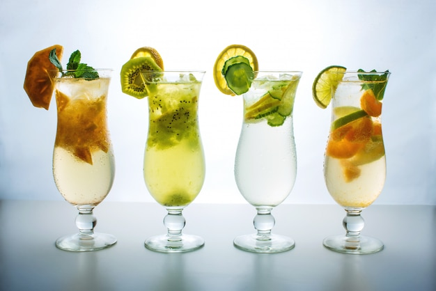 Set lemonade with ice in glass hurricane with tropical fruits Premium Photo