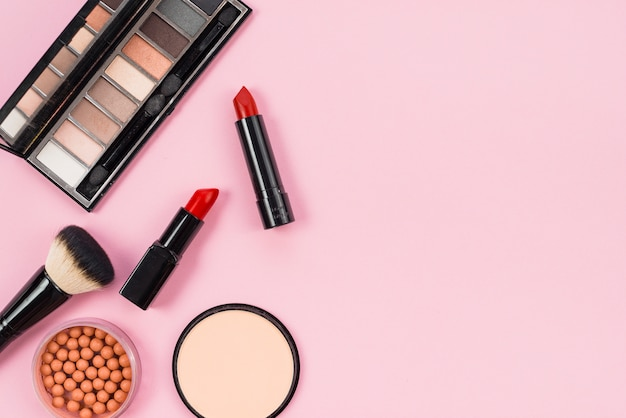 Set of makeup and cosmetic accessories on pink background Free Photo