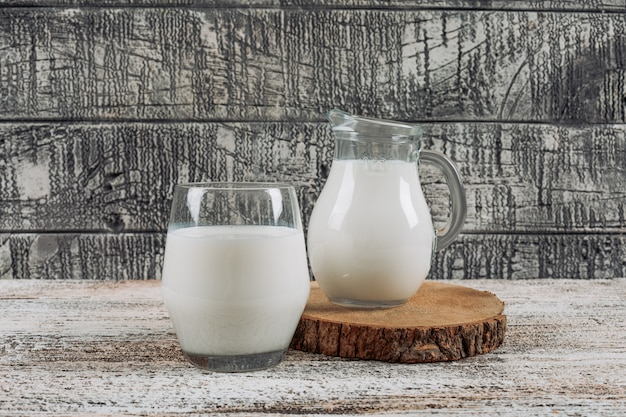 Set di caraffa del latte e bicchiere di latte in una fetta di legno su un fondo di legno grigio. vista laterale. Foto Gratuite