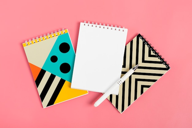 Set of notebooks for notes and pens on pink background place for text flat lay Premium Photo