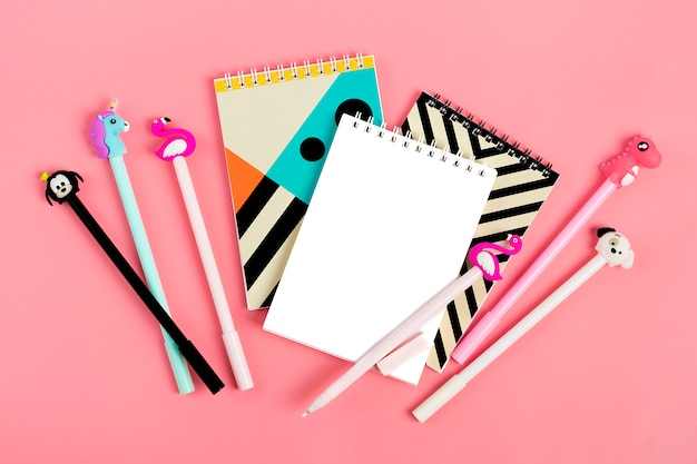 Set of notebooks for notes and pens on pink background Premium Photo