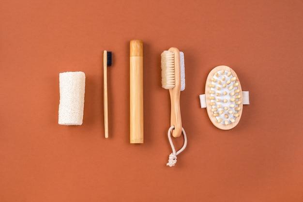 Набор аксессуаров для ванной. антицеллюлитный массажер, бамбуковая зубная щетка, губка из люфы, кисточка для пилинга на коричневом. концепция нулевых отходов. минималистичный стиль. Premium Фотографии
