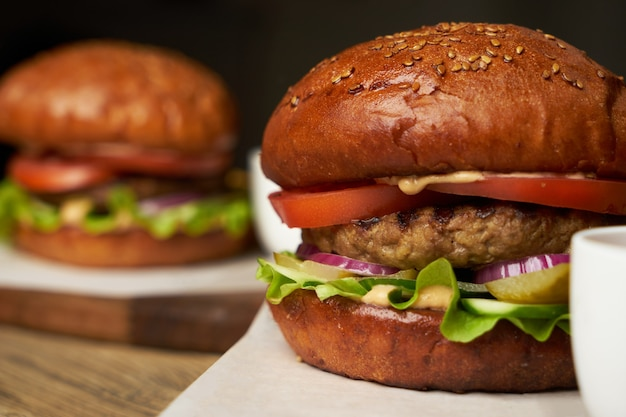 감자 튀김과 케첩 소스와 함께 햄버거 세트. 큰 햄버거와 감자 튀김 나무 테이블 배경. 패스트 푸드는 배경을 설정합니다. 레스토랑 버거 메뉴 프리미엄 사진