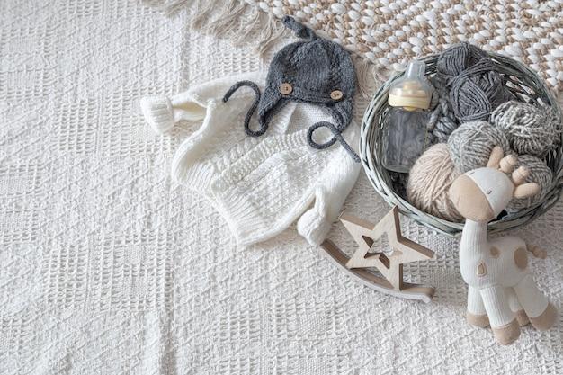 Набор детской стильной вязанной одежды ручной работы с различными аксессуарами в стиле бохо, вид сверху. Бесплатные Фотографии